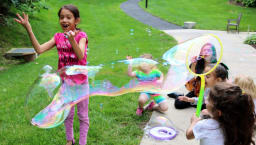 Alumna Grace A. blowing bubbles with children