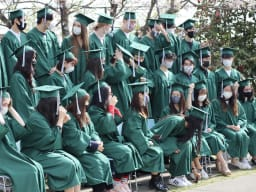 Boys and girls in green gowns posing for a photo