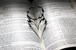 An open Bible with the crown of thorns