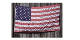 US Flag displayed on the side of a an aged barn.