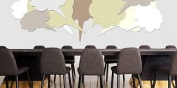 Conference room tables with empty chairs around it and multiple idea bubbles above the table