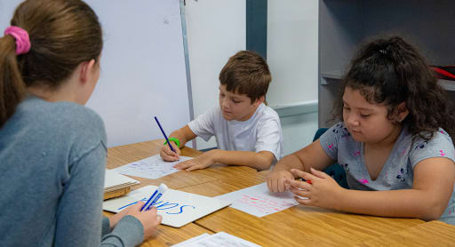 A teacher works on reading skills with a young boy and young girl.