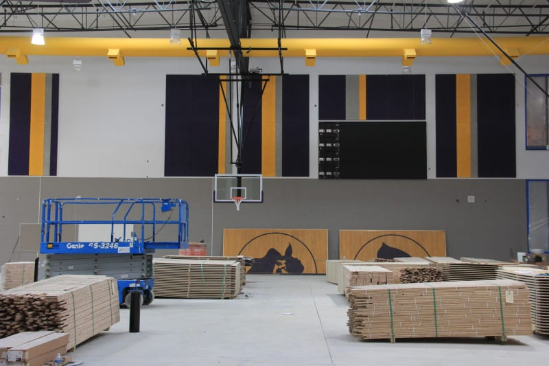 View of new HHS gym with yellow-gold ductwork, basketball hoop and piles of wood flooring.