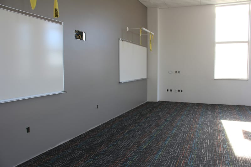 View of classroom with paint, whiteboards and carpet.