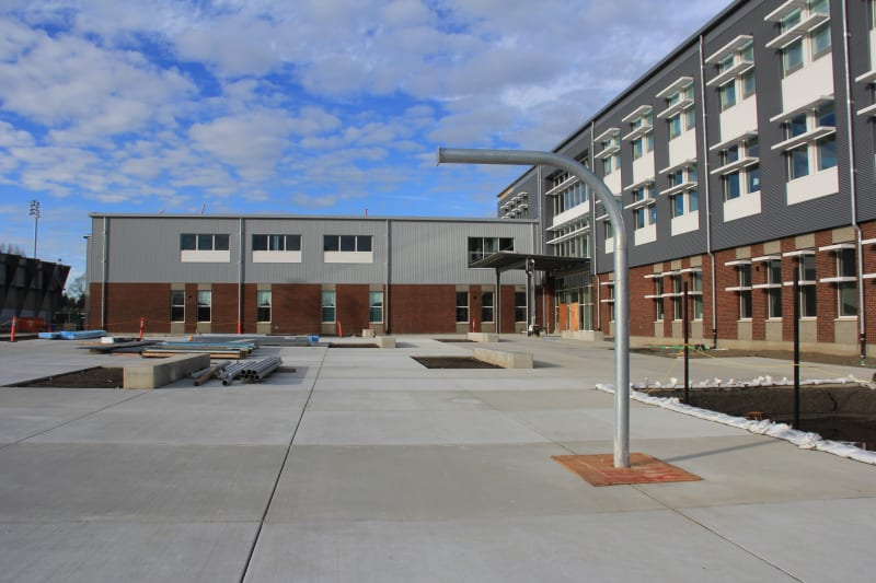 View of south courtyard with post for outdoor basketball hoop and outdoor seating.