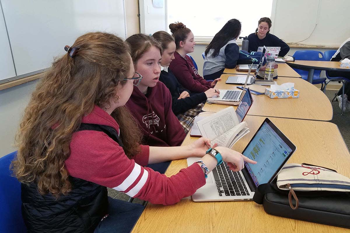 Girls collaborate on a script on a laptop