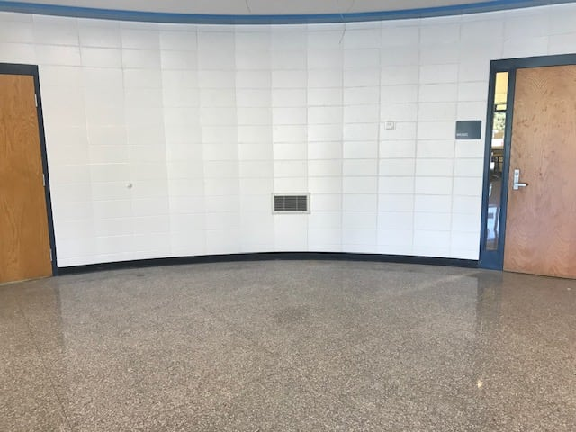 Image of the lobby wall between the music and art room. Currently white block wall in between two doors.