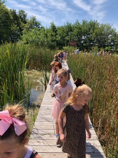 Image of children walking on the deck in the Cole Outdoor Education Center Wetlands