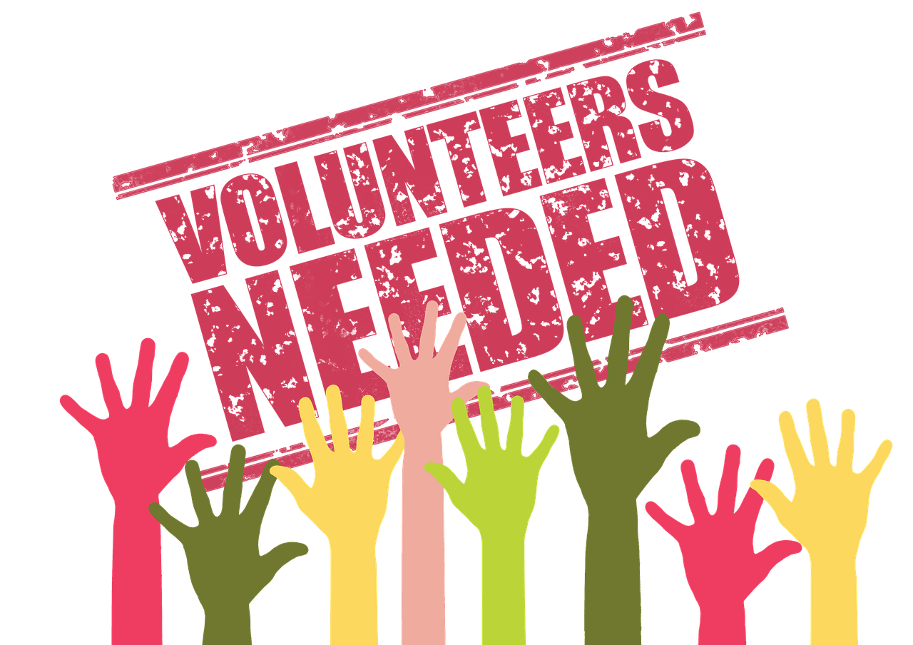 Hands Raised and Phrase ''Volunteers Needed''