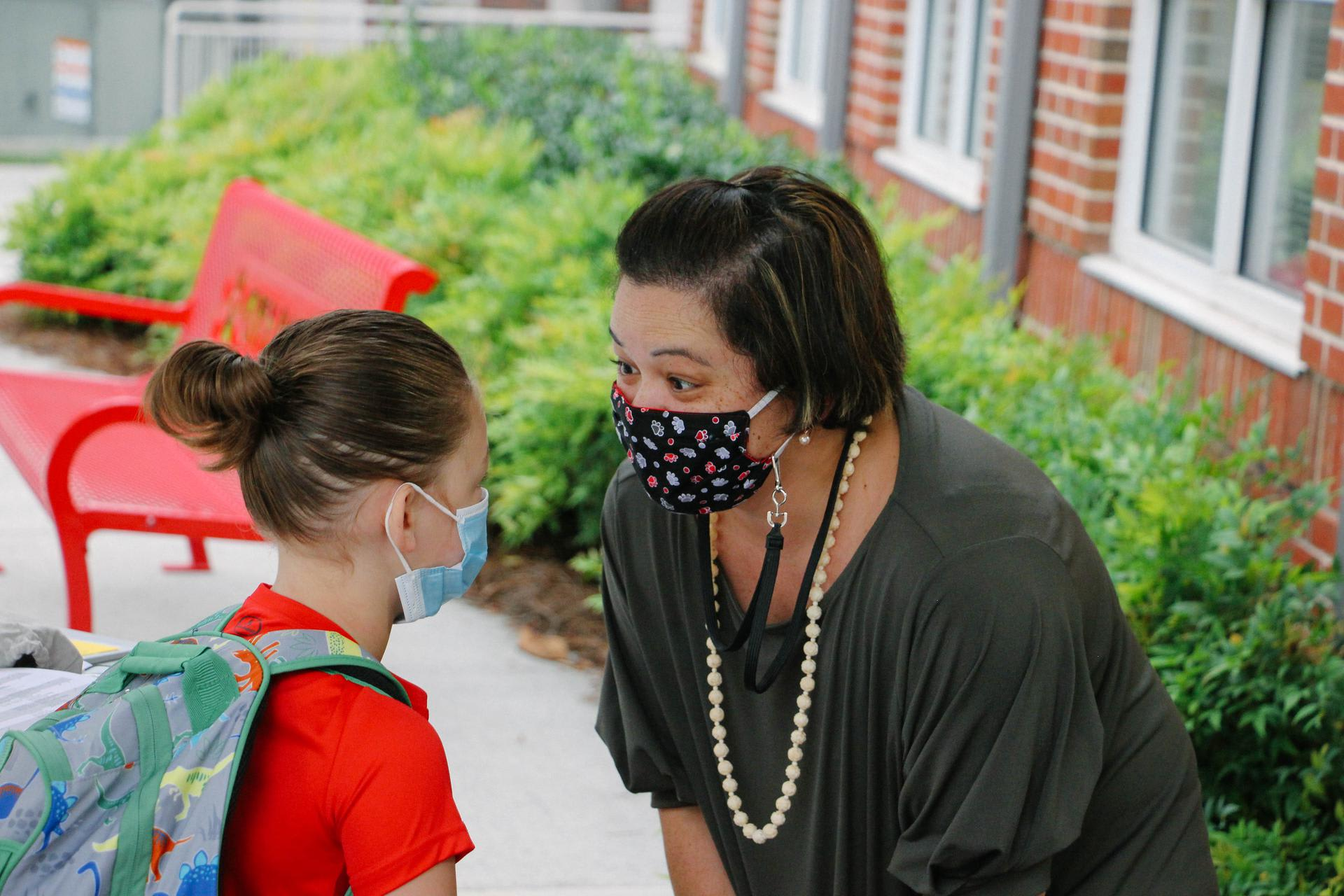 Teacher greeting student with mask on