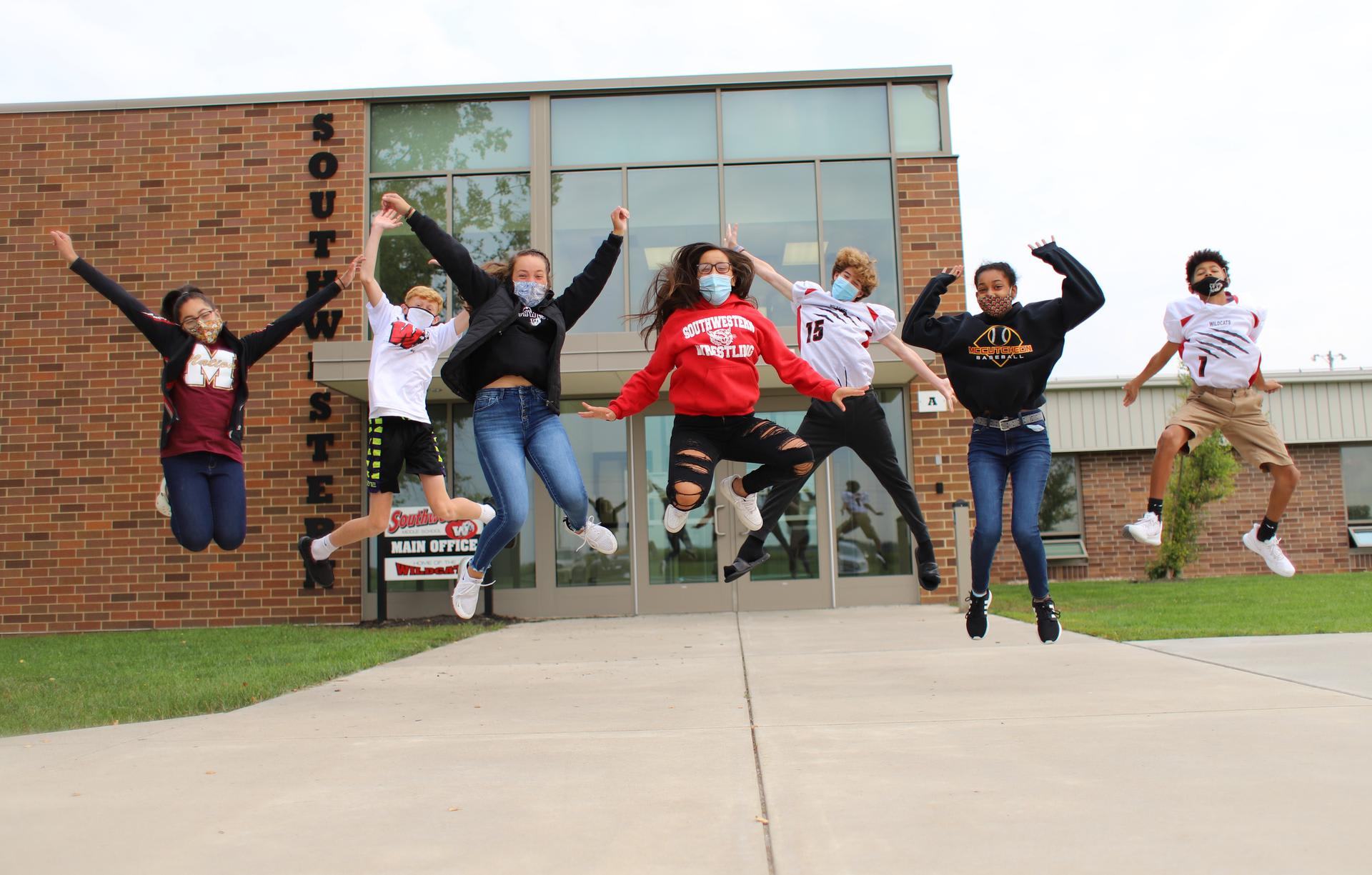 9 Students Jumping in front of Southwestern Middle School