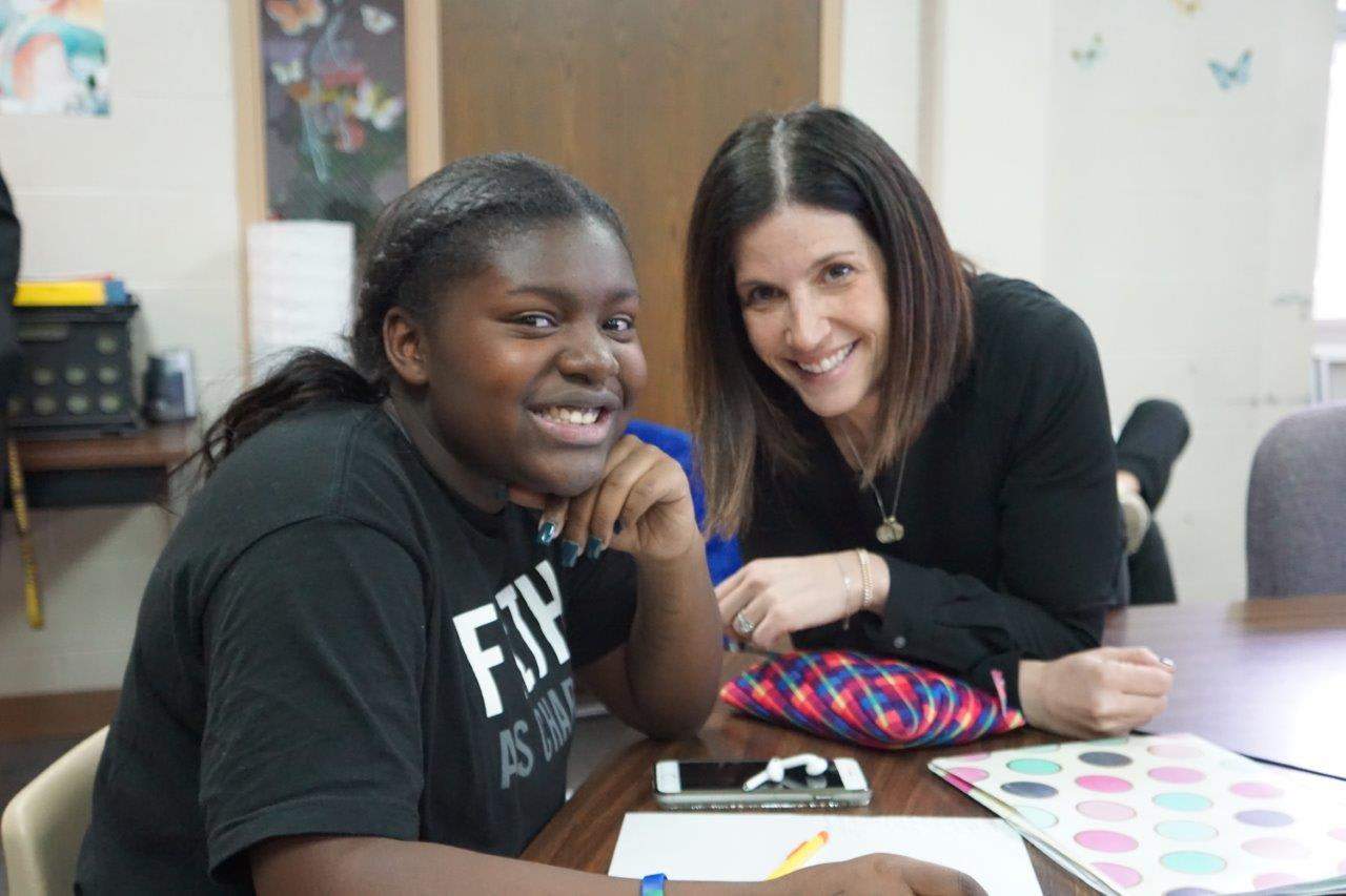 A staff member works with a student.