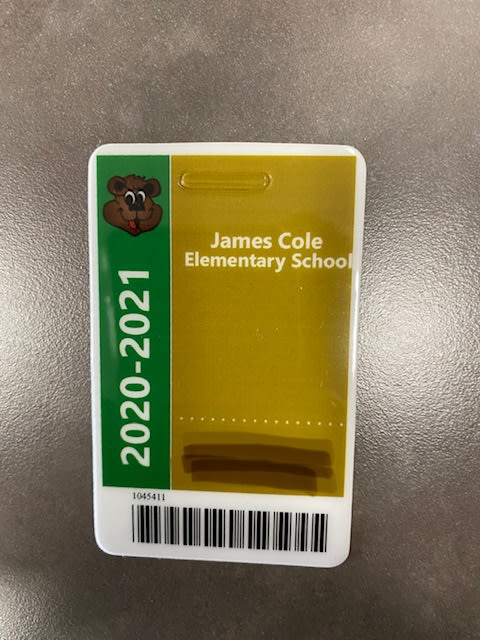 Picture of a school bus ID badge with 2020-2021 on the right side in white letters with a green background and a gold background on the right with James Cole Elementary School written in white. A barcode is across the bottom of the ID badge.