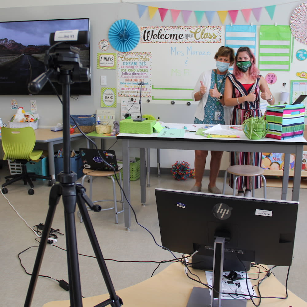teachers prepping computer and cameras in classroom