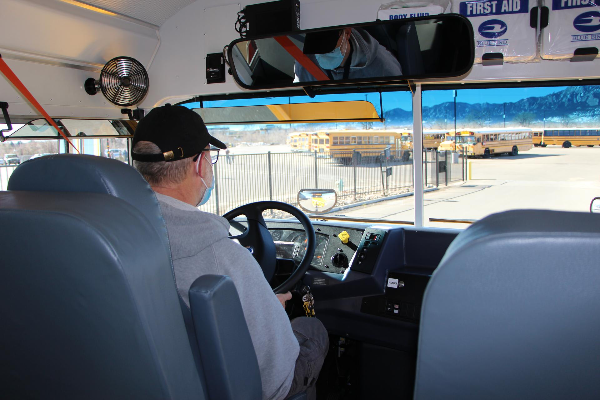 bus driver in new electric bus at bus depot