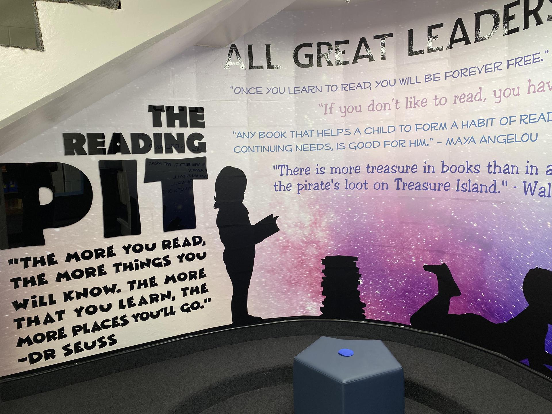 Picture of the new graphics on the Cole Reading Pit in the Library. Includes silhouettes of children reading and quotes from authors about reading. Black lettering with purples, blues, and starry background.