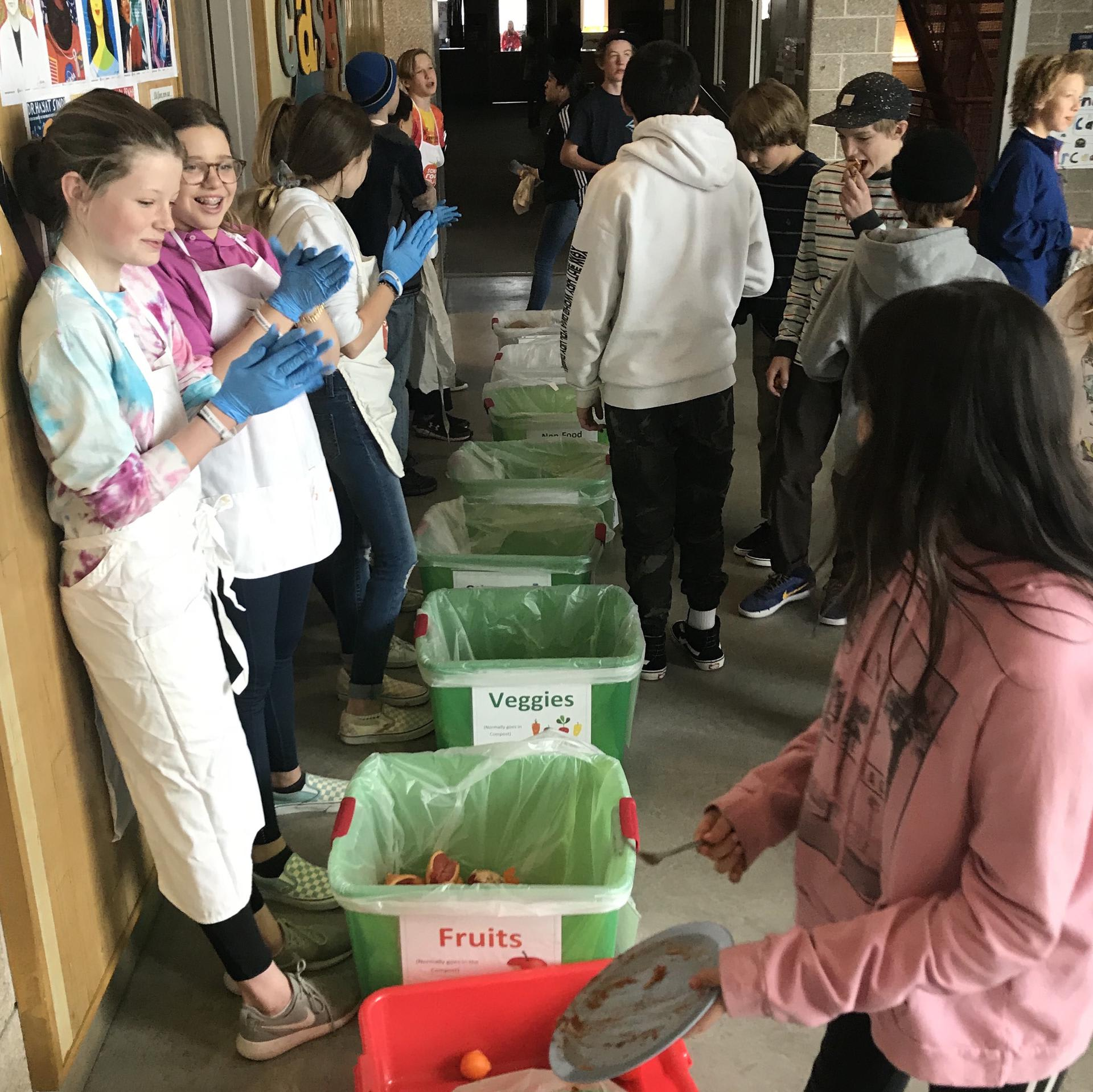 students helping sort waste in cafeteria