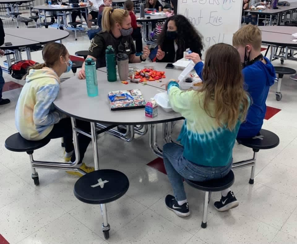 SRO Kidwell sitting at a lunch table with students.