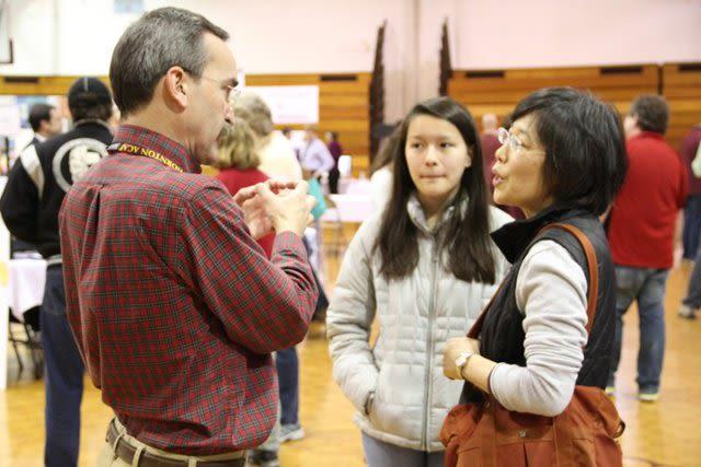 A family talks with a teacher at the Thornton Academy Academic Expo