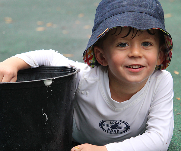 Child Smiling with Bucket