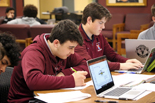 two students in maroon quarter zips working with open laptop facing them