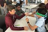 one student guides hands of another while building tower with pasta